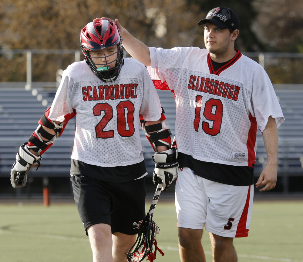 Scarborough junior varsity lacrosse player Teddy Prosack, right, gives a pat on the head to teammate Austin Pietras after his shift May 1 during a game at Fitzpatrick Stadium. Both players will be at Autism Awareness games Saturday.