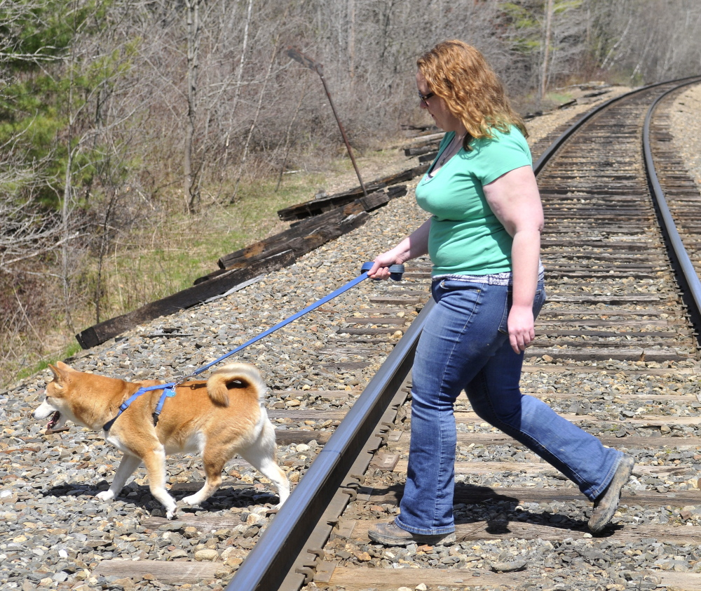 Miriam Easton and her dog cross one of the two train tracks that bisect her family's 80 acres in Oakland on Thursday. A long train on the tracks blocks a trail that the Easton family has maintained for generations.