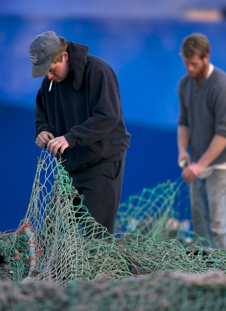 Fishermen Ed Stewart, left, and Tannis Goodsen mend groundfishing nets on Merrill Wharf in Portland last year.