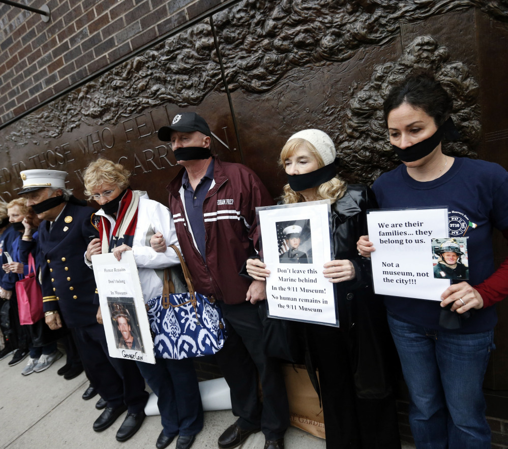 Family members of victims of the Sept. 11, 2001, attacks wear black gags over their mouths in protest of the transfer of unidentified remains to the World Trade Center site.