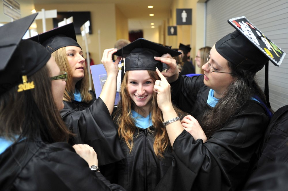 Sarah Quint, center, of Wells gets her cap securely pinned to her hair by fellow graduates Krista Chamberlain of Buxton, second from left, and Melissa Adams of Biddeford, right, as they get ready for the USM graduation procession at Cumberland County Civic Center in Portland on Saturday. Each received a master's degree in teaching and learning.