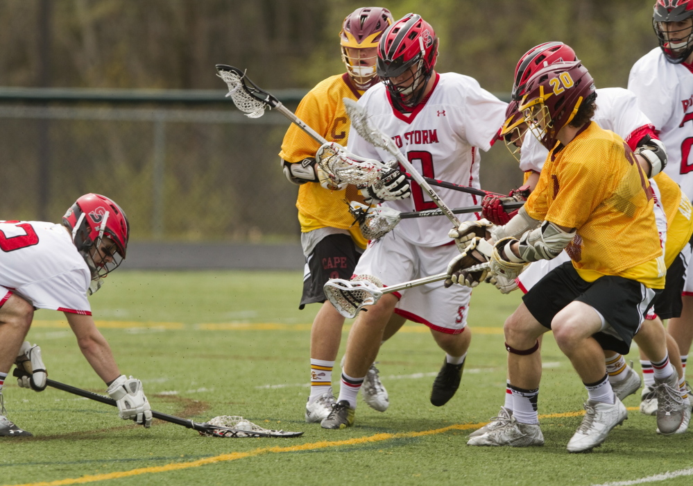 Scarborough goalie Jordan Flannery, left, covers the ball as a crowd of Cape Elizabeth and Scarborough players move in during a boys' lacrosse game at Scarborough on Saturday. Unbeaten Cape Elizabeth handed the Red Storm their first loss of the season, 10-5.