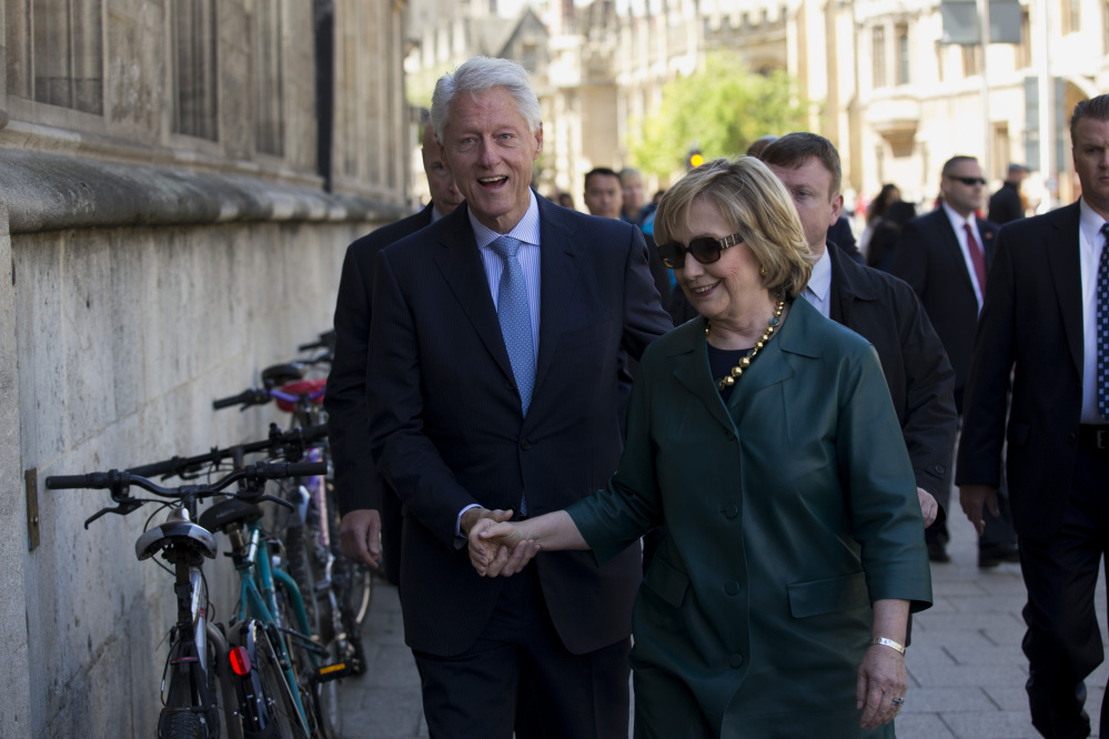 Former U.S. President Bill Clinton, left, and his wife former Secretary of State Hillary Rodham Clinton walk into a building entrance after they attended their daughter Chelsea's Oxford University graduation ceremony held at the Sheldonian Theatre in Oxford, England, on Saturday.