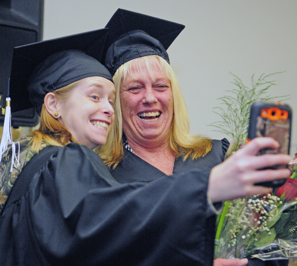 "Nicole ""Sis"" Trask, left, takes a picture with her mother, Kathy Trask, on Saturday before they walked in the University of Maine at Augusta graduation ceremony."