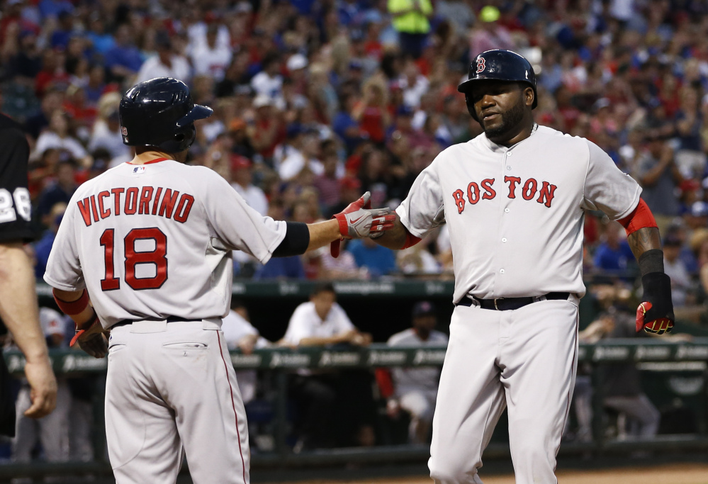 Red Sox designated hitter David Ortiz, right, and outfielder Shane Victorino congratulate each other after scoring on a hit by Jonny Gomes in the fourth inning of Saturday's game against the Texas Rangers in Arlington, Texas.