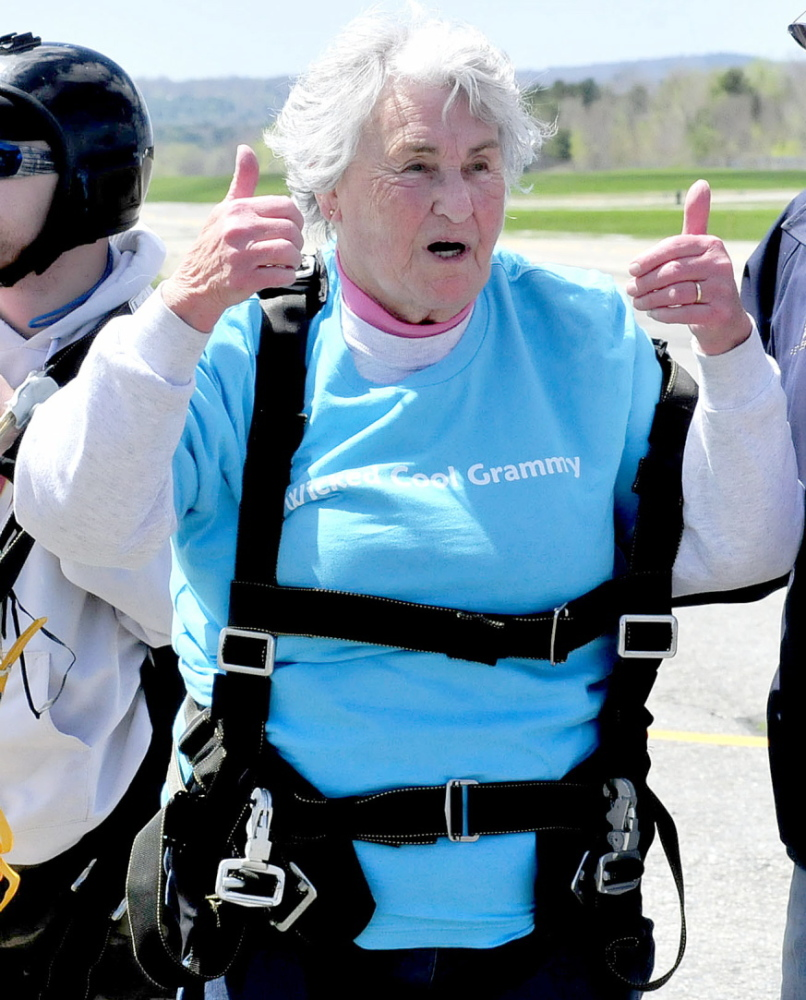 Marjorie Bell, who turned 80 on Saturday, gives the thumbs-up sign to family members after she successfully skydived in tandem at LaFleur Airport in Waterville.