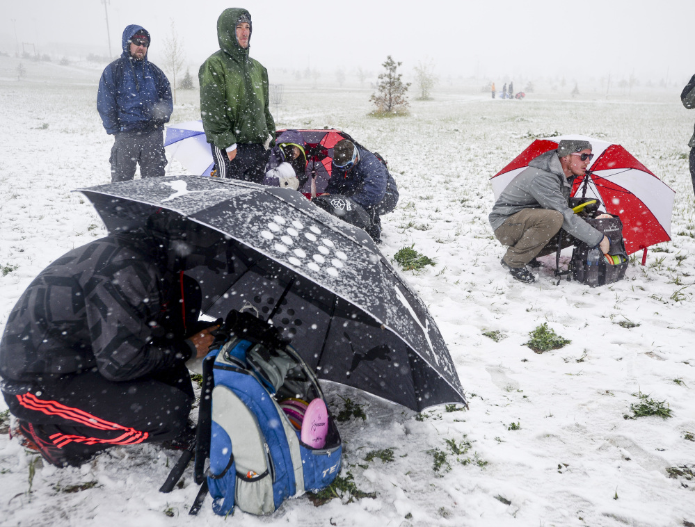Disc Golf players shield themselves from the snow and wind with umbrellas as they compete in a tournament Sunday in Fort Collins, Colo. Snow is expected to fall through Monday, with highs reaching the 60s later this week.