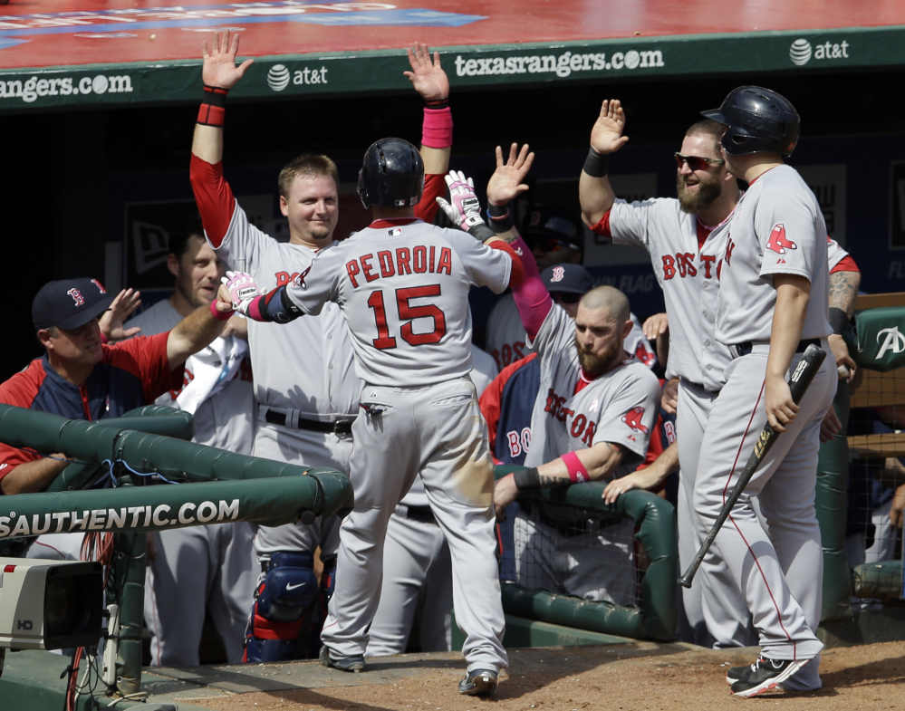 Boston's Dustin Pedroia is congratulated by Manager John Farrell, left, catcher A.J. Pierzynski and Mike Napoli, second from right, following his solo home run off Robbie Ross of the Rangers in the seventh inning Sunday.