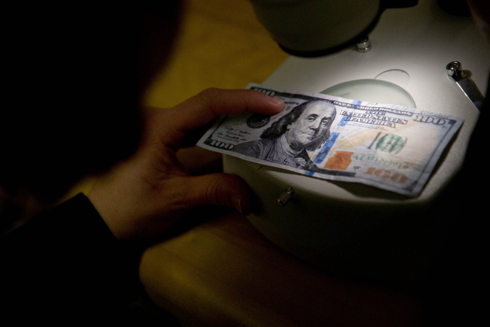 Counterfeit specialist Marybeth Dellibovi demonstrates inspecting a counterfeit $100 bill under a microscope at Secret Service headquarters in Washington, D.C.