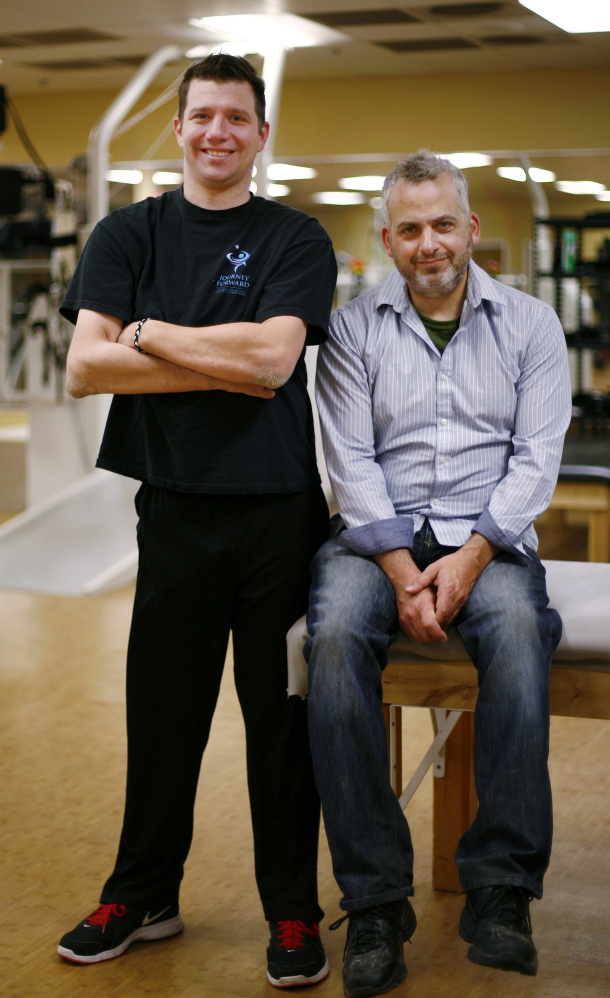 Documentary filmmaker David Fresina, right, poses with Dan Cummings at Journey Forward, Cummings' center to help people recover from spinal cord injuries in Canton, Mass.