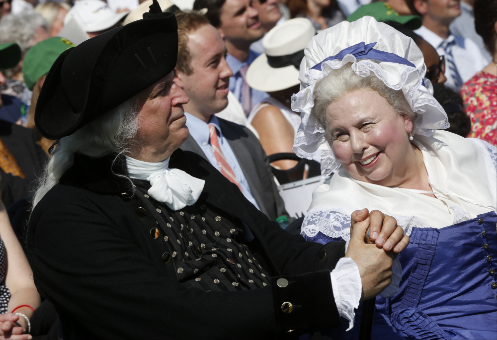 George Washington, played by Dean Malissa, left, and Martha Washington, played by Mary Wiseman, attend a ceremony to celebrate the reopening of the Washington Monument on Monday. The monument sustained damage from an earthquake in August 2011.