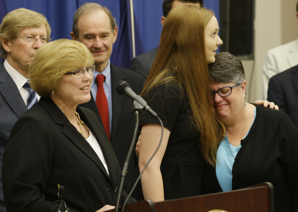 Plantiffs in the federal suit over Virginia's ban on gay marriage, Mary Townley, left, Emily Schall-Townley, center, and Carol Schall react to comments during a news conference after a hearing on Virginia's same sex-marriage ban in Richmond on Tuesday.
