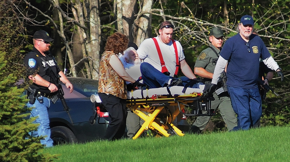 Walter Nolan, father of Michael Nolan, is escorted by police officers as he is taken on a stretcher from his home in Brentwood, N.H., on Monday. Michael Nolan is believed to have killed a police officer before setting the house afire and dying in the blaze.