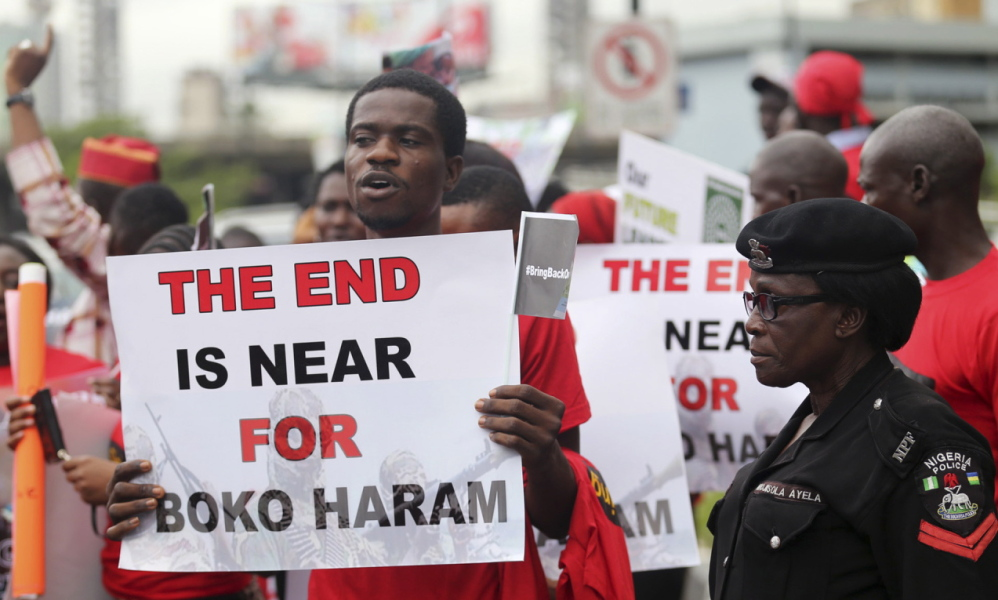 A security officer, right, stands by as people hold placards calling for the release of secondary school girls abducted in the remote village of Chibok, Nigeria.