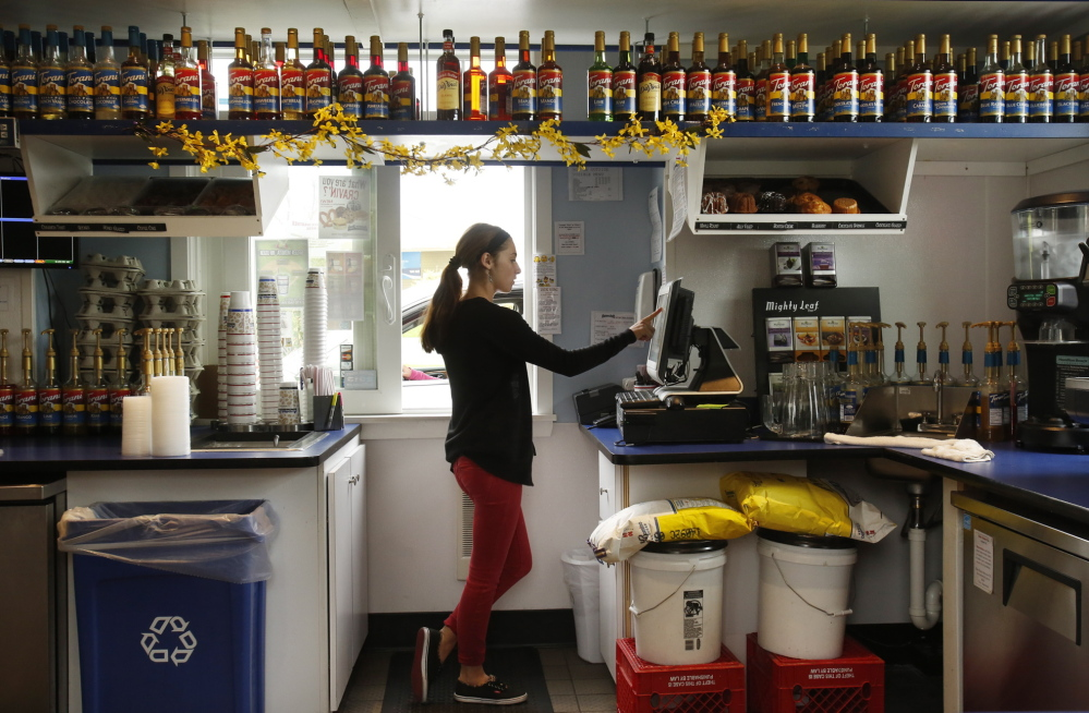 Tori Monagle takes an order at the Aroma Joe's drive-thru in Saco on Monday. The company that prides itself on greeting customers by name plans to open kiosks in northern Massachusetts and Vermont in June.