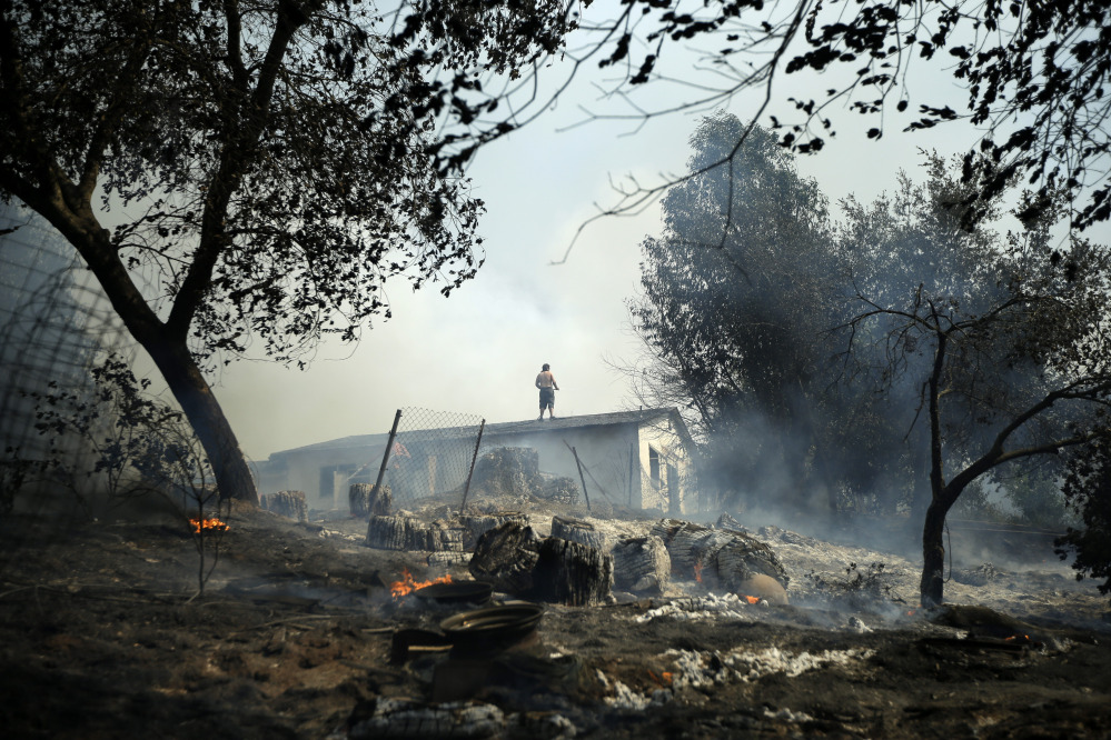 Jeff Brown waters the roof of his home as vegetation smolders during a wildfire Thursday in Escondido, Calif.