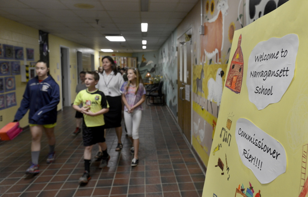 Fifth-graders Danielle Eid, Nathan Eichner and Alison Walker change classes Thursday at the Narragansett School in Gorham. The school's grade jumped from a C to an A, earning a visit from Education Commissioner Jim Rier.