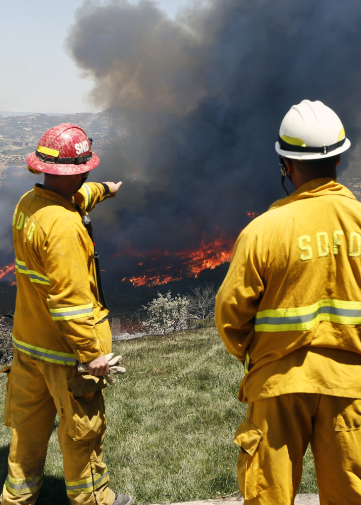 Firefighters plan their attack as a brush fire flares up, heading toward homes Thursday in San Marcos, Calif., north of San Diego.