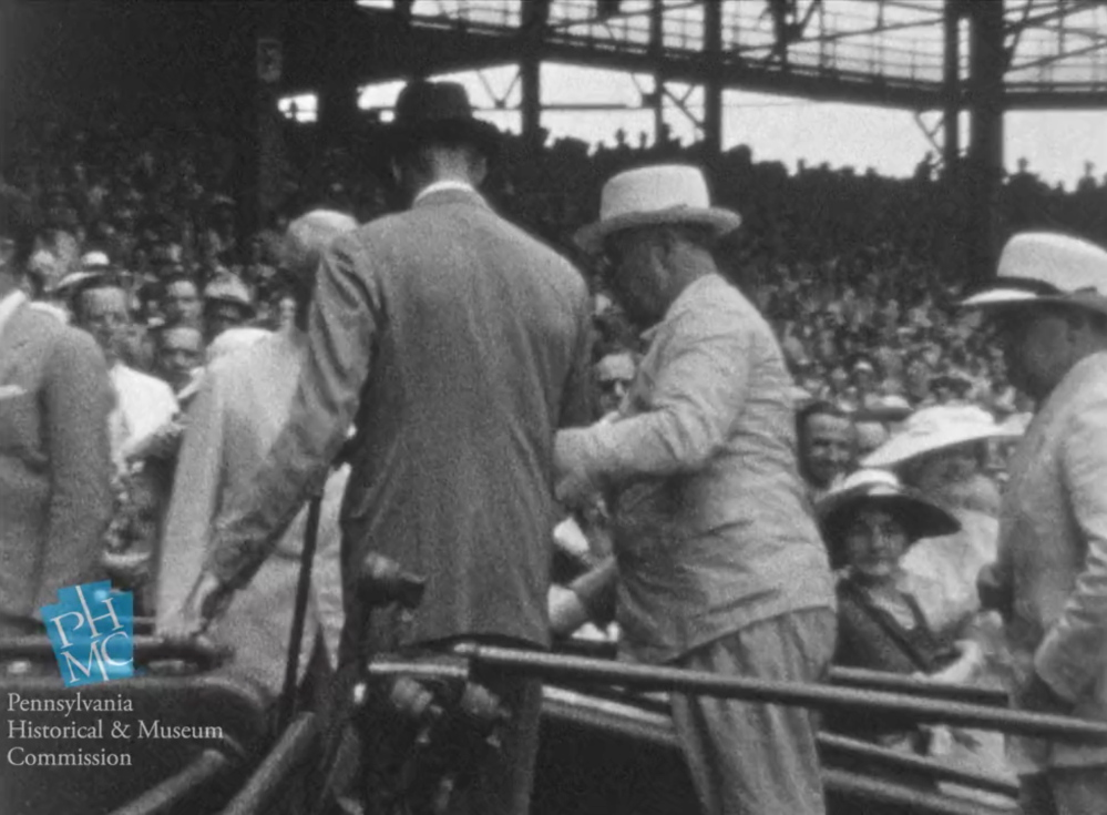 In this image taken from film shot by former Major League Baseball player Jimmie DeShong, President Franklin D. Roosevelt, center, walks to his seat with the aid of an assistant at the baseball All-Star game on July 7, 1937, at Griffith Stadium in Washington.