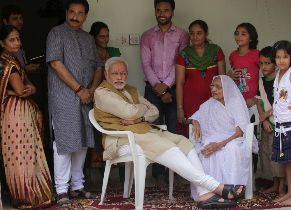 Opposition Bharatiya Janata Party leader Narendra Modi sits with his 90-year-old mother, Hiraben, during a visit to seek her blessings after preliminary results showed his party winning by a landslide, in Gandhinagar, in the western Indian state of Gujarat on Friday. Modi will be India's next prime minister, winning the most decisive election victory the country has seen in more than a quarter century and sweeping the long-dominant Congress party from power, partial results showed Friday.