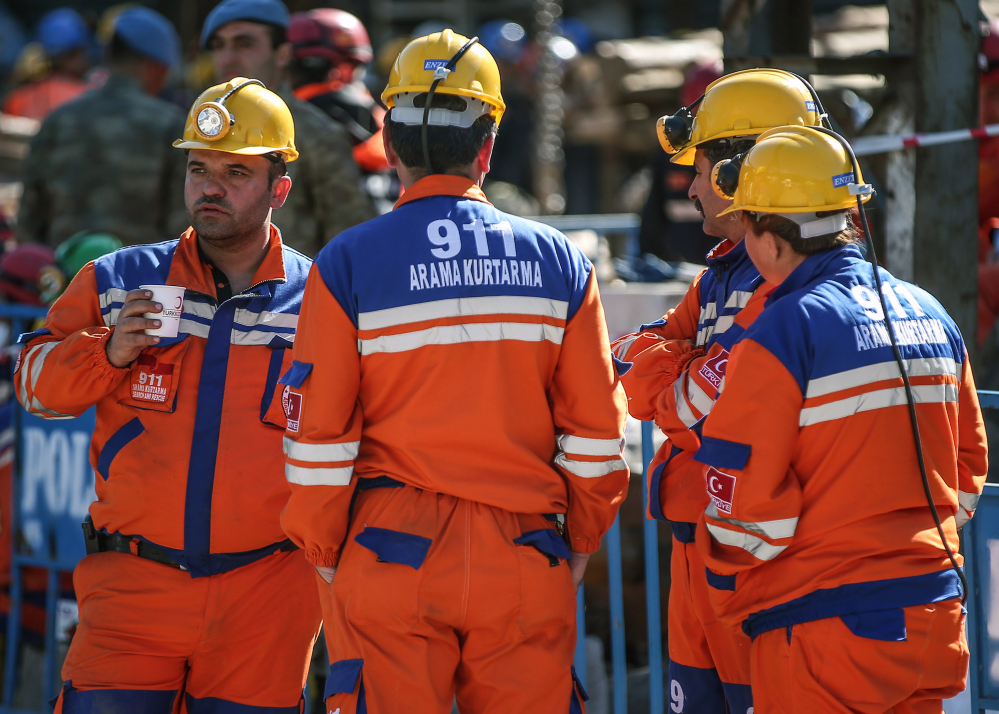 Turkish rescue workers stand at the entrance of the coal mine in Soma, Turkey, Friday. A Turkish mining company defended its safety record Friday, four days after over 250 people died in an underground blaze at its coal mine in western Turkey.