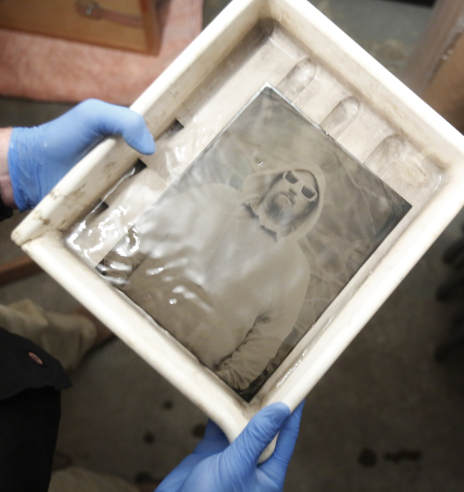 Mark Dawson watches as a tintype photograph emerges in a tray of developer.