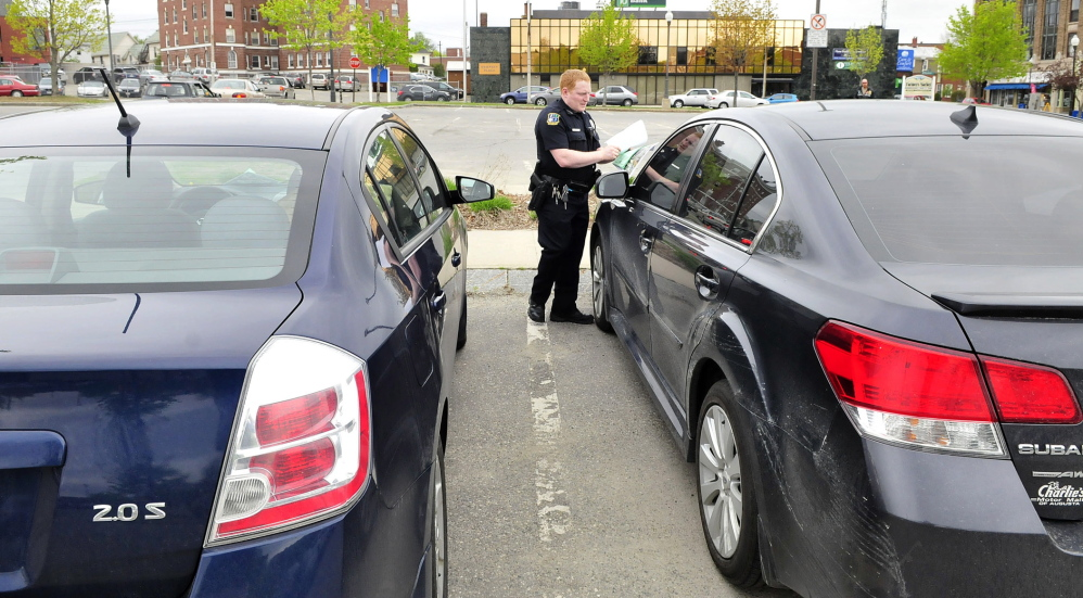 Waterville police Officer Robert Bouley places a map with new parking regulations in The Concourse and a warning that the car was parked longer than the two-hour maximum in Waterville on Thursday.