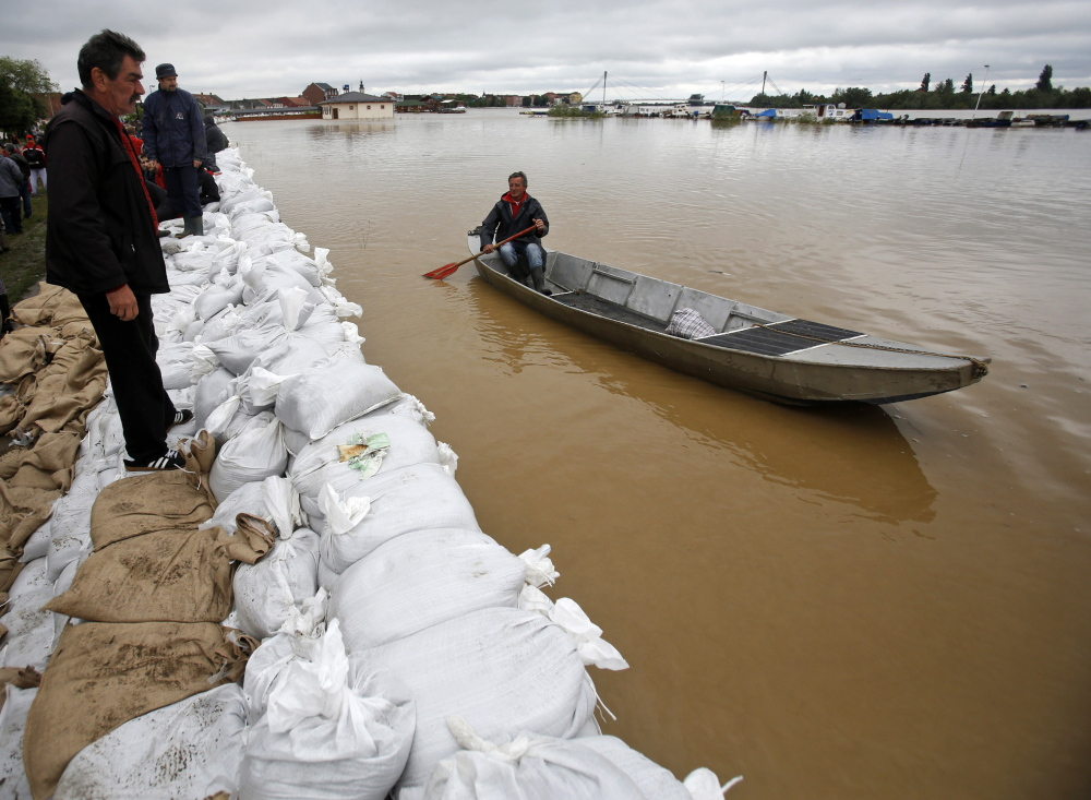 A man steers a boat along the sandbag-lined banks of the Sava River in Sremska Mitrovica, Serbia, on Saturday. Seen from the air, almost a third of nearby Bosnia resembles a lake.