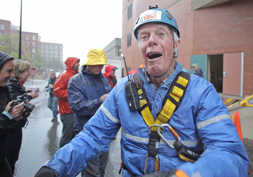 John Parker, 83, of Falmouth celebrates after rappelling down the side of One City Center in Portland as part of a fundraiser.