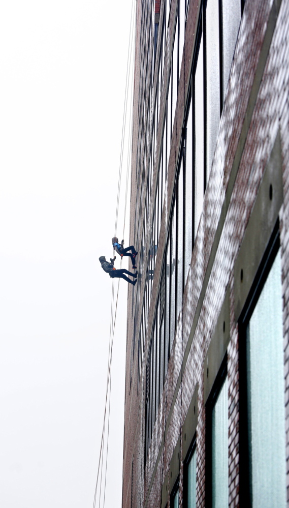 Racheal Delcourt, top, and Richard Veilleux, who both work at MaineHealth, rappel down One City Center during Rappel for Rippleffect on Saturday in Portland.