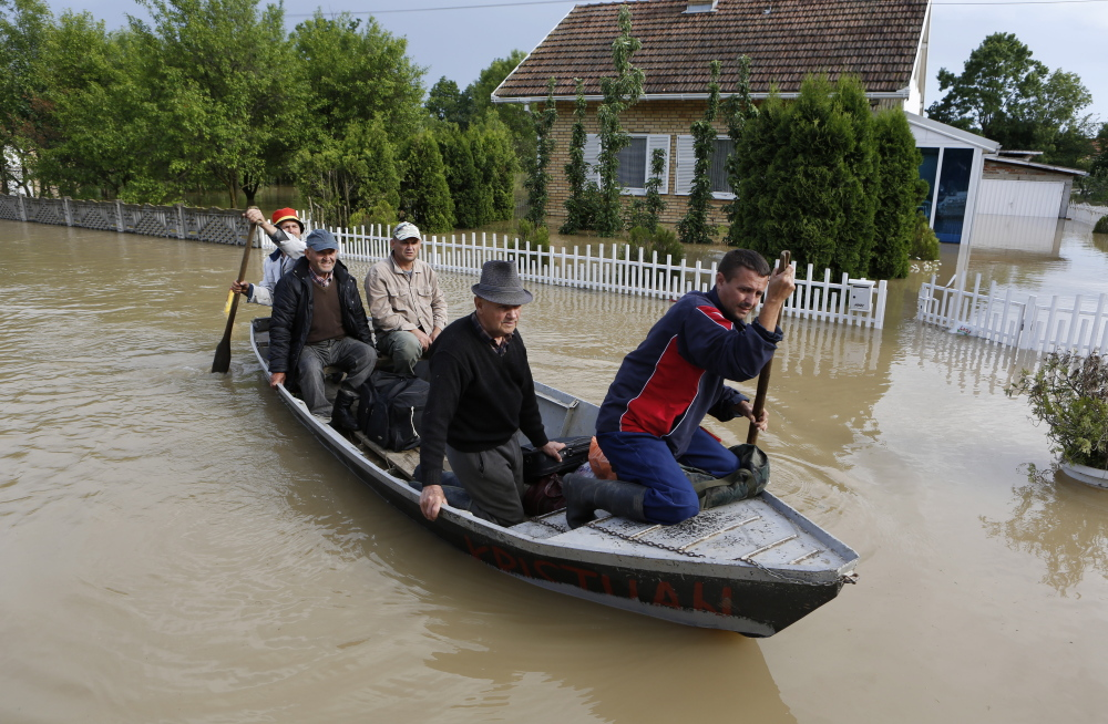 Bosnians are rescued by boat from their flooded houses Sunday in the village of Vidovice. Packed into buses, boats and helicopters, carrying nothing but a handful of belongings, tens of thousands have fled their homes in Bosnia and Serbia.