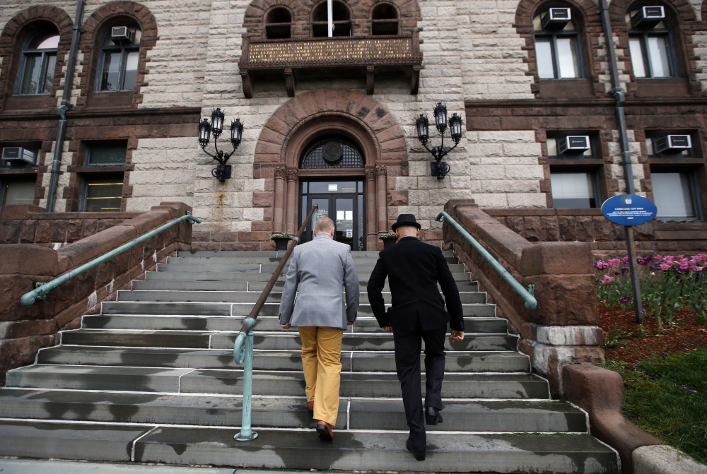 """Scott Bechaz, left, and Carlos Franca walk up to Cambridge City Hall in Cambridge, Mass., on Friday to be married. The Republican Party platform defines marriage as """"a union between a man and a woman"""" but attitudes may be changing."""