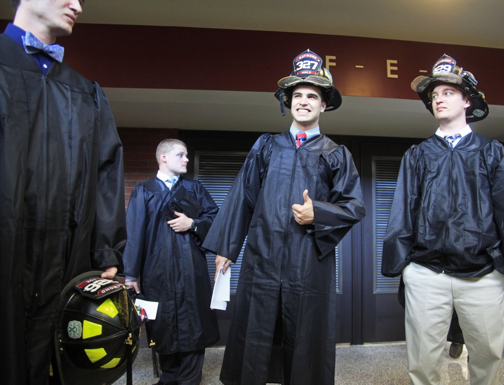 Hunter Holt, center, is already partially geared up for his career while he waits with other fire science graduates before Sunday's ceremony.