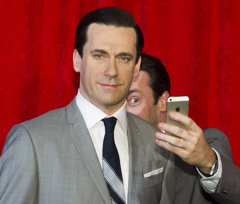 Actor Jon Hamm, the live one, takes a selfie at the unveiling of his wax figure at Madame Tussauds in New York. Selfie is one of the 150 new words appearing in Merriam-Webster's Collegiate Dictionary.
