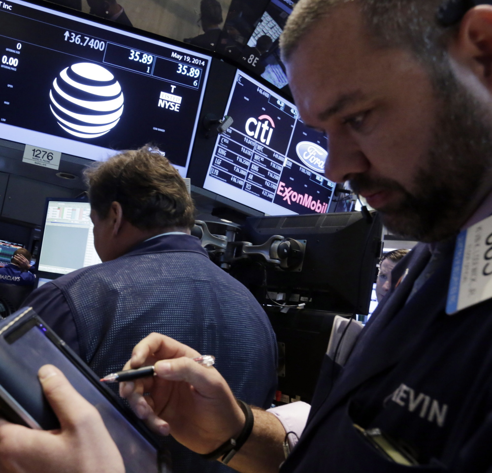 Traders gather at the post that handles AT&T on the floor of the New York Stock Exchange on Monday. AT&T Inc. announced it would buy DirecTV for $48.5 billion in cash and stock.