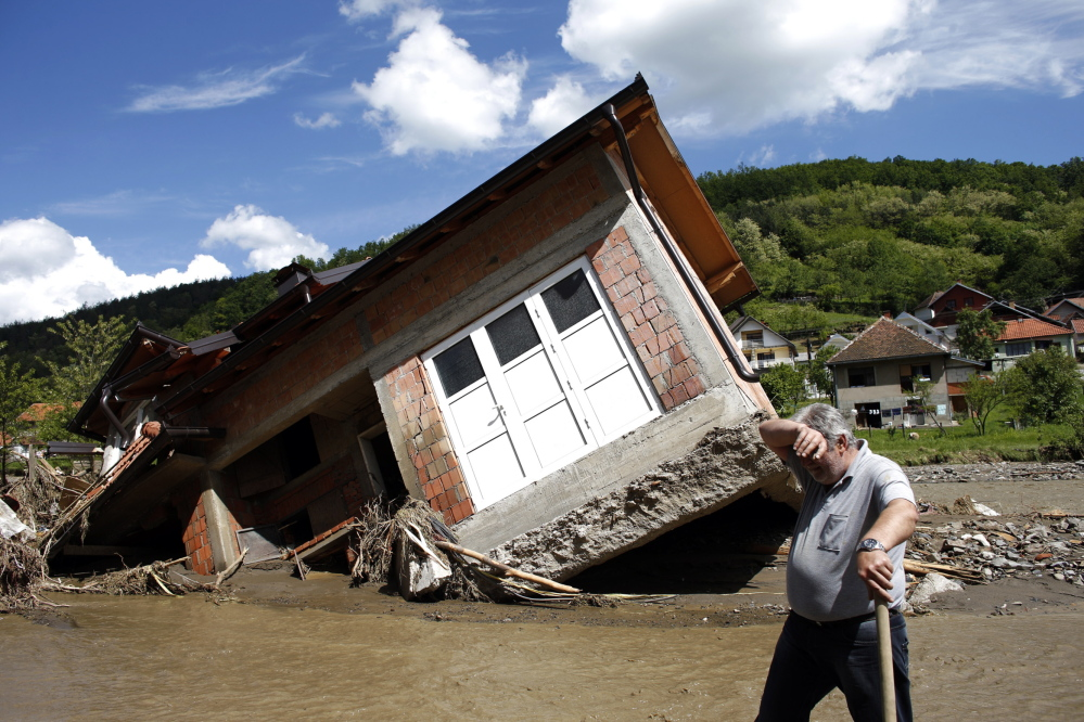 A man works near a house tilted by floods in the village of Krupanj, west of the Serbian capital of Belgrade. Communities in Serbia and Bosnia battled to protect towns and power plants from rising floodwaters and continued landslides Monday.