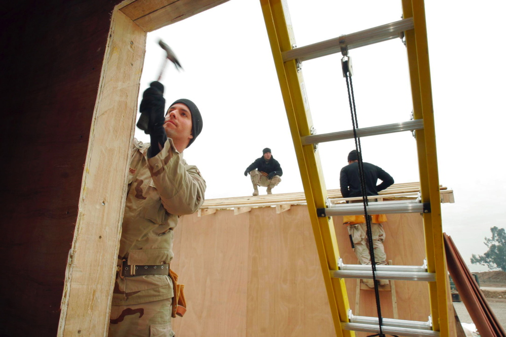 In this December 2004 file photo, Sgt. Todd Kiilsgaard of Westbrook of the 133rd Engineer Battalion of the Maine Army National Guard hammers a trim board on the front of a building that will be used by the Iraqi National Guard at a traffic control point near Mosul. The adjutant general of the Maine Army National Guard is scheduled to meet with Gov. Paul LePage this week amid a controversy over plans to swap Maine's 133rd Engineer Battalion for an infantry unit from another state.