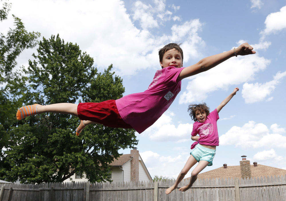 Xavier Delgado, left, and his sister Haley Delgado play on the trampoline in the yard in their new home in Moore, Okla. Xavier was trapped under rubble following the May 20, 2013, tornado at Plaza Towers Elementary school, and Haley was knocked out by debris.