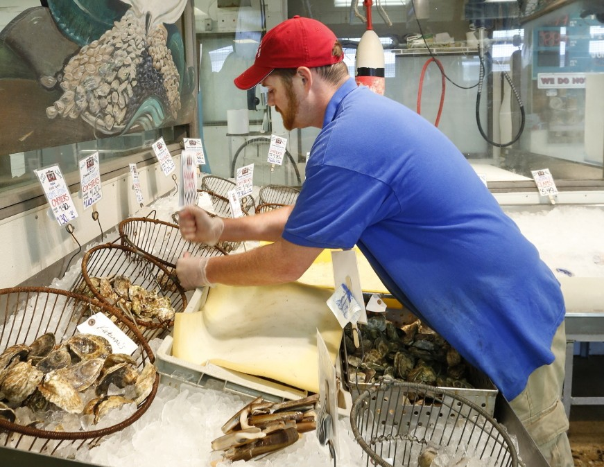 """Retail manager Dan Kraus stocks shellfish Monday at Harbor Fish Market on the Portland waterfront. In a survey of nearly 600 Mainers, two-thirds of respondents said they had bought """"fish, seafood or shellfish"""" in the past month, but only 47 percent of it came from Maine waters."""