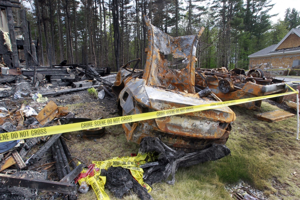 Burnt cars are seen in Brentwood, N.H., on Monday, in the front of a house where Officer Stephen Arkell was shot and killed after responding to a domestic dispute. Authorities say the house was set on fire, and leaking propane caused an explosion.