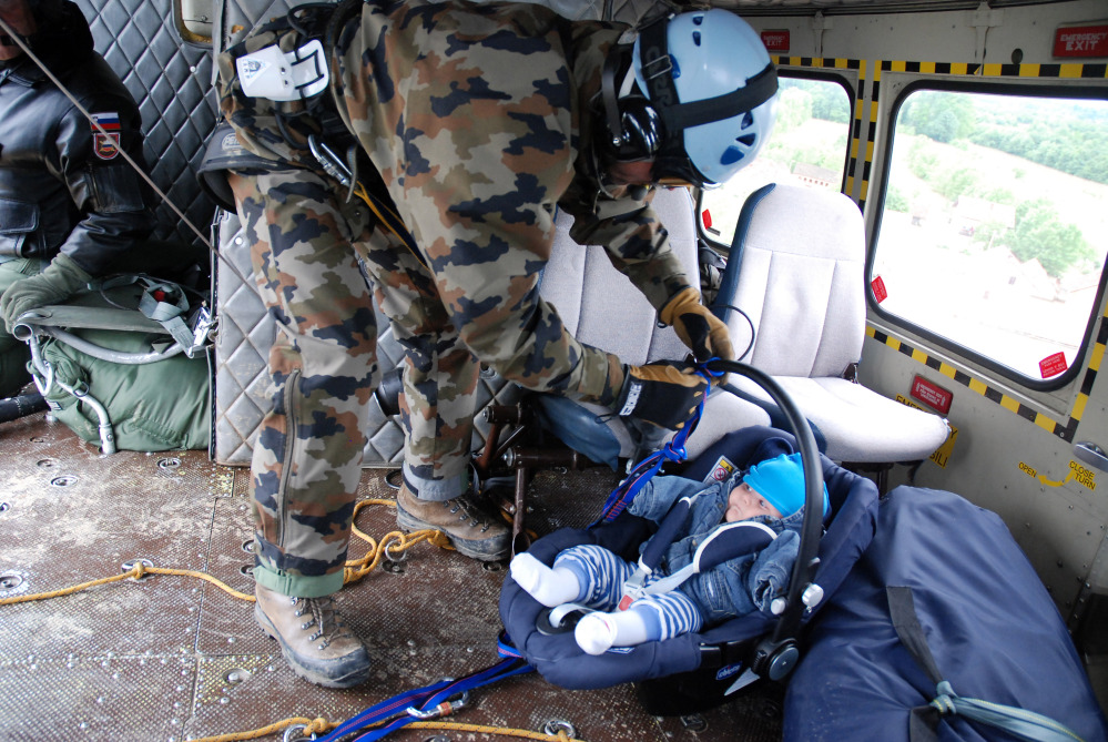 A Slovenian army helicopter team rescues a baby by winching the baby carrier into the helicopter over the village of Tisina in northern Bosnia-Herzegovina last week. The rest of the baby's family was evacuated later on, the rescue team said.