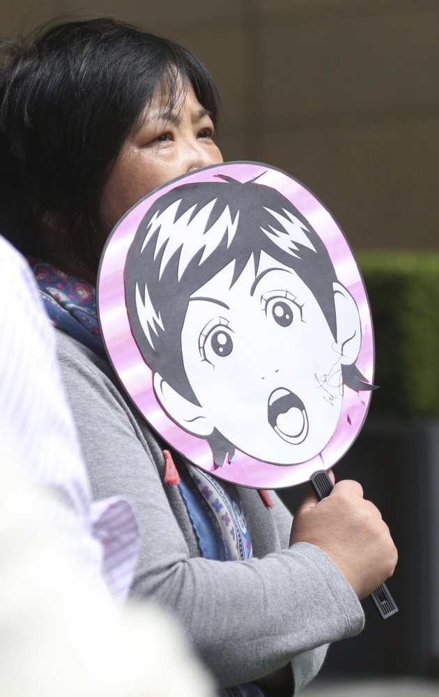 A fan of Paul McCartney waits outside a hotel where he is thought to be staying Tuesday in Tokyo.