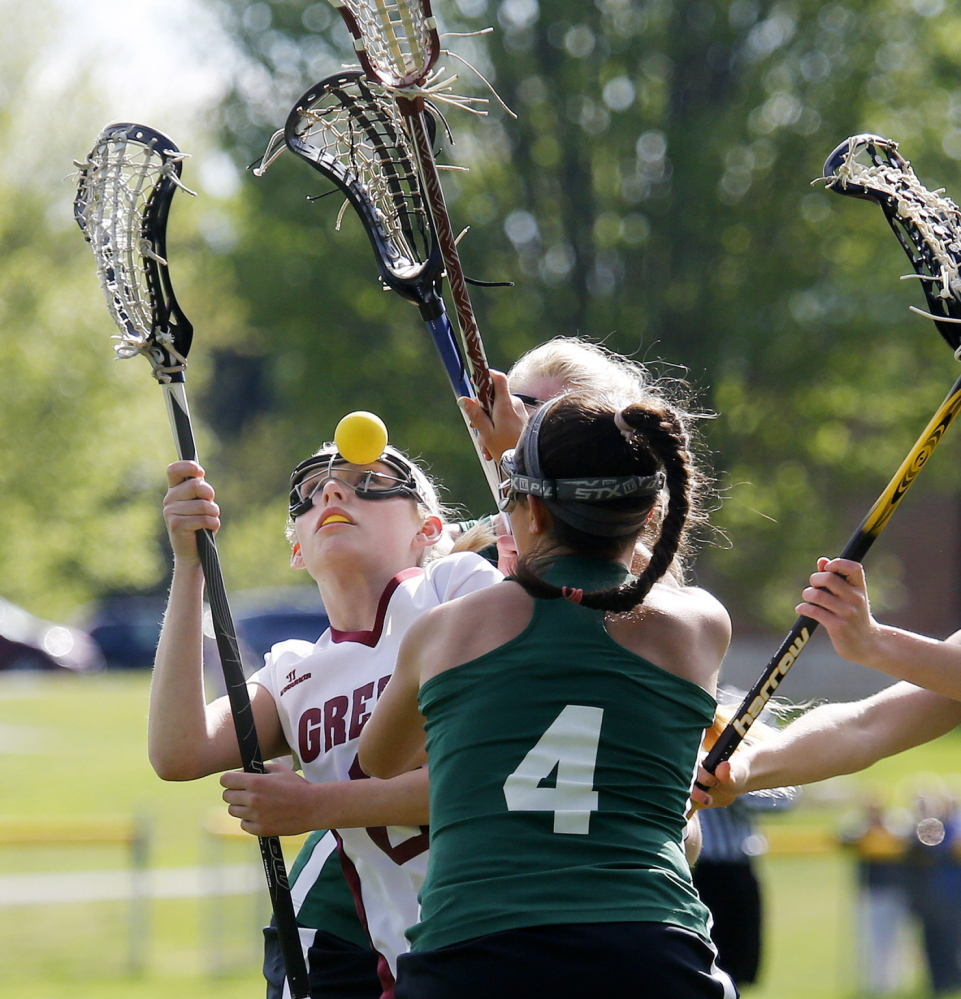 Cameron Keefe of Greely gets a close look – a darn close look – at the lacrosse ball Wednesday while attempting to find a way through Waynflete's defense, including Sofia Canning, foreground. Greely had opportunities but ended up falling 11-8 to a team that's won six straight Western Maine championships.