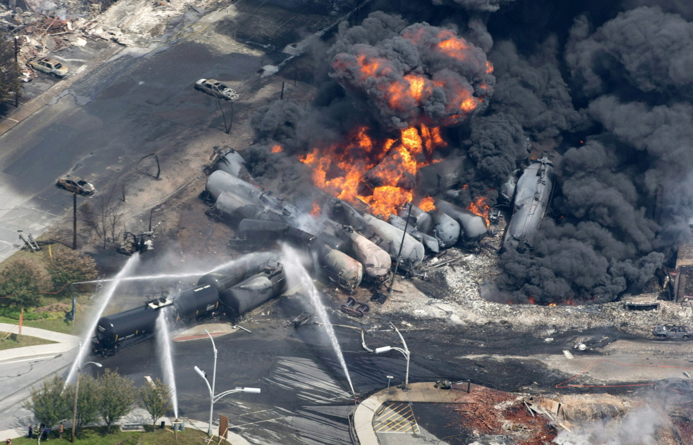 Smoke rises from flaming railway cars that were carrying crude oil after a train derailed in downtown Lac-Megantic, Quebec, in July 2013. Forty-seven people died in the resulting fire. The tragedy has raised significant issues that should be resolved before the new owner of the same railroad creates a timetable for reviving the oil transport link.
