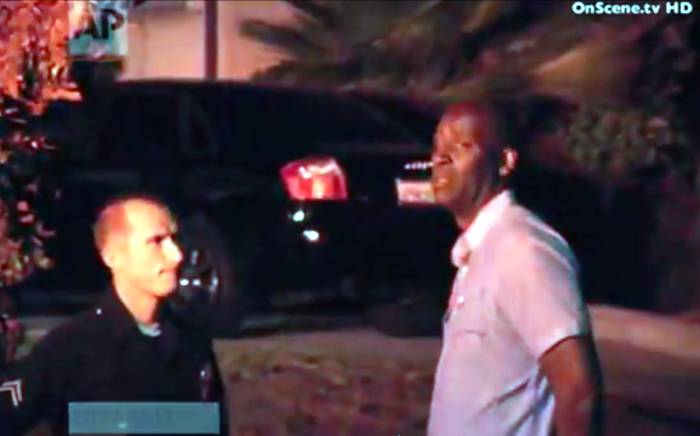 In this image taken from video from OnScene.tv, actor Michael Jace, right, is detained by police outside his home in Los Angeles on Monday night. Jace, who played a police officer on the hit TV show