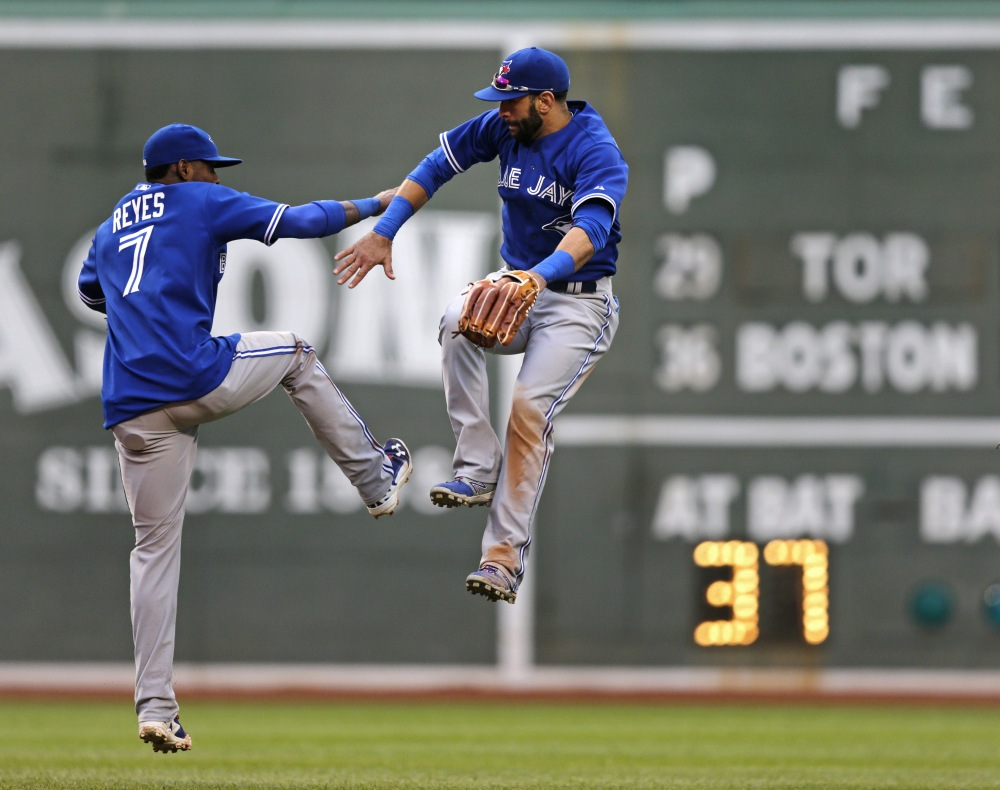 Toronto Blue Jays right fielder Jose Bautista, right, leaps as his celebrates with teammate Jose Reyes after the Blue Jays defeated the Boston Red Sox in a baseball game at Fenway Park, Thursday, May 22, 2014, in Boston. Bautista went 3-for-5 with two RBIs in the Blue Jays' 7-2 win.
