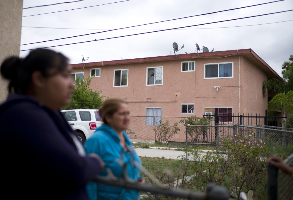 Neighbors chat Thursday near the building where Isidro Garcia lived in Bell Gardens, Calif., with a woman he is accused of kidnapping a decade ago.