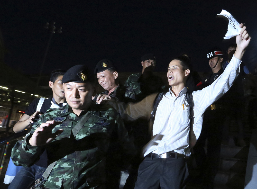 Thai soldiers detain Apichat Pongsawat, right, an activist who staged a protest against the coup in downtown Bangkok, Thailand, on Friday.