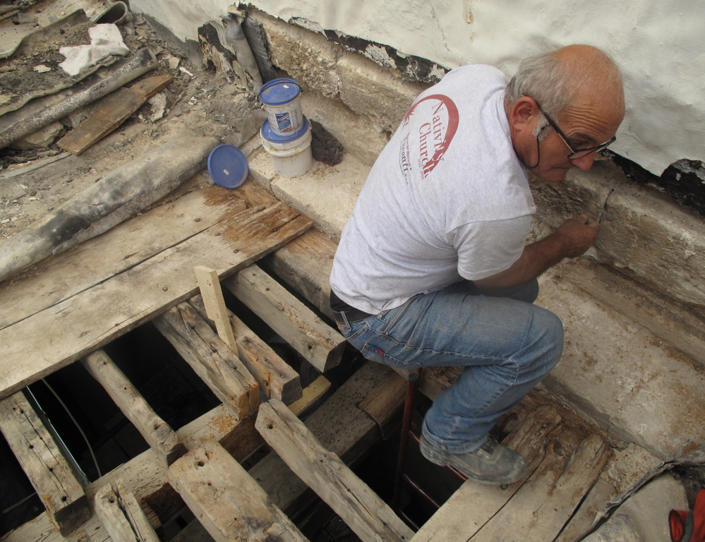 A craftsman from an Italian restoration company repairs the roof of the Church of the Nativity in Bethlehem.