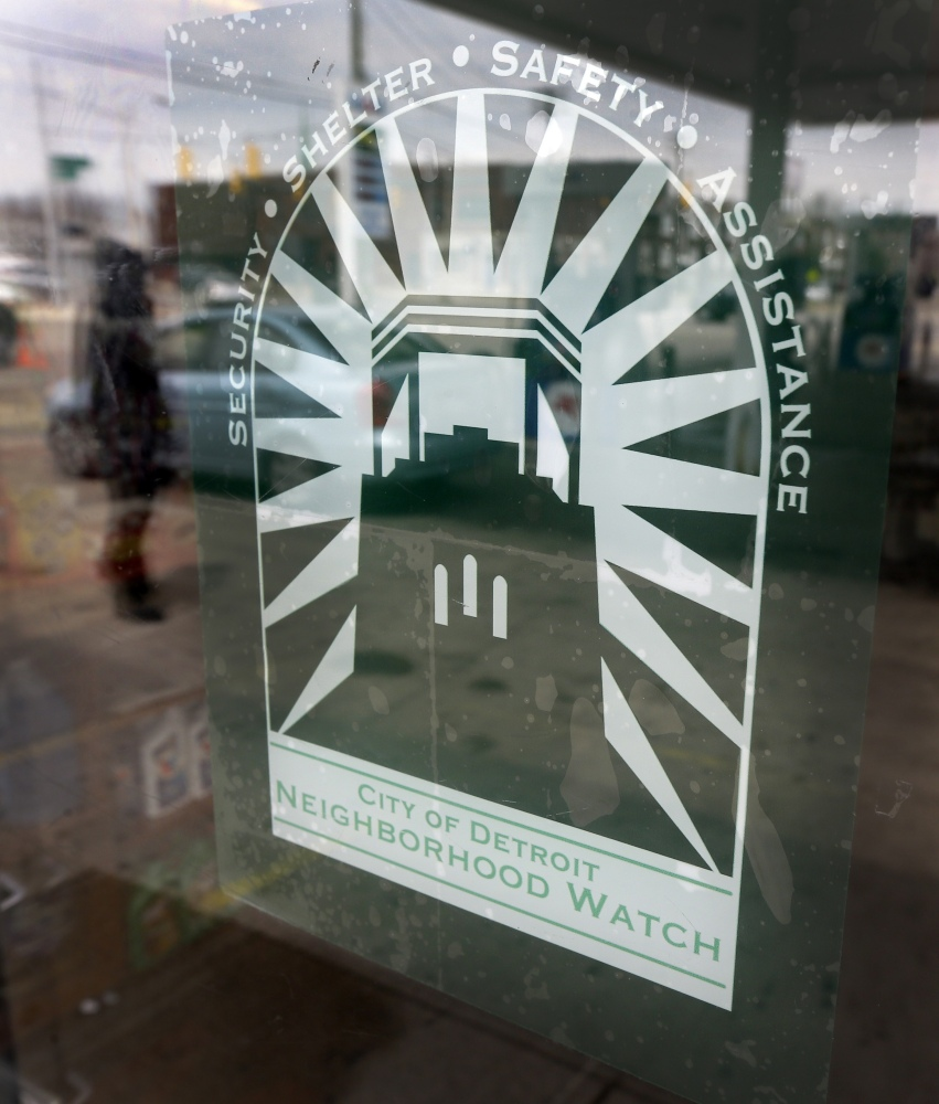 A decal highlighting shelter, safety and assistance is displayed on the front door of Mousa Bazzi's Mobil station on Detroit's east riverfront.